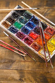 Colourful watercolors and brushes on wooden background  — Stok fotoğraf