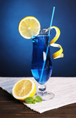 Glass of cocktail on table on dark blue background — Stock Photo