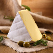 Tasty Camembert cheese with thyme and olives, on wooden table — Stock Photo #41700043