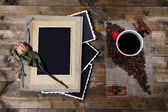 Composition with coffee cup and photo album, on wooden background — Stockfoto
