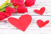 Paper hearts with flowers on wooden background — Stock Photo