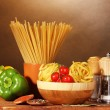 Spaghetti, noodles in bowl, paprika tomatoes cherry on wooden table on brown background — Stock Photo