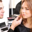 Young guy stylist doing makeup beautiful woman in beauty salon  — Stock Photo #41763653