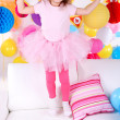 Pretty little girl jumping on sofa on celebratory background — Stock Photo