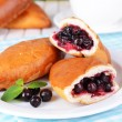 Fresh baked pasties with currant on plate on table close-up — Stock Photo #41765561