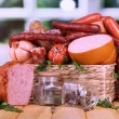 Lot of different sausages in basket on wooden table on window background — Stock Photo #41766501
