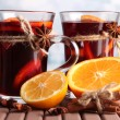 Stock Photo: Mulled wine with oranges and spices on table on bright background