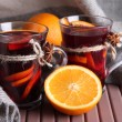 Stock Photo: Mulled wine with oranges on table on fabric background
