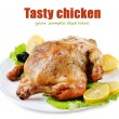 Whole roasted chicken with vegetables on plate, isolated on white — Stock Photo