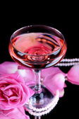 Composition with pink sparkle wine in glass and  rose isolated on black — Stock Photo