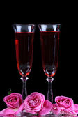 Composition with pink sparkle wine in glasses and  roses isolated on black — Stock Photo