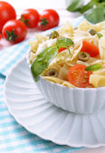 Delicious pasta with tomatoes on plate on table close-up — Stockfoto