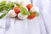 Tasty mozzarella cheese with basil and tomatoes, on wooden table — Stockfoto
