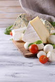 Different tasty cheese, on wooden table — Stock Photo