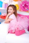 Vrij klein meisje, zittend op de Bank op feestelijke achtergrond — Stockfoto