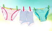 Baby clothes hanging on clothesline, on bright background — Stock Photo