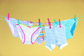 Baby clothes hanging on clothesline, on color background — Stock Photo