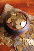 Golden coins in ceramic pot, on wooden background — Stockfoto