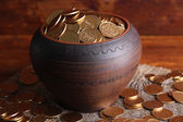 Golden coins in ceramic pot, on wooden background — Stock Photo