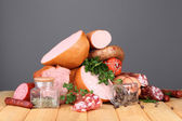 Lot of different sausages on wooden table on grey background — Stock Photo