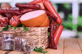 Lot of different sausages in basket on wooden table on window background — Stockfoto