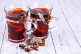 Mulled wine with spices on wooden background — Stock Photo