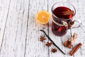 Mulled wine with lemon and spices on wooden background — Stock Photo
