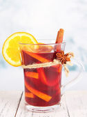 Mulled wine with orange and spices on table on bright background — Stockfoto
