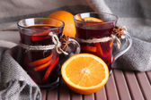 Mulled wine with oranges on table on fabric background — Stockfoto