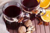 Mulled wine with oranges and nuts on table close up — Stock Photo