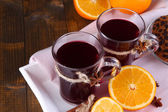 Mulled wine with oranges and spices on table close up — Stock Photo