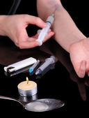 Drug addict with syringe in action on black background — Stock Photo