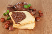Bread with sweet chocolate hazelnut spread on wooden background — Stock Photo