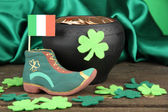 Saint Patrick day boot, pot of gold coins and clover leaves on green satin background — Stock Photo