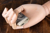 Money in wooden hand, on  wooden background — Stock Photo