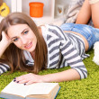 Young woman resting with book on fluffy carpet, near sofa at home — Stock Photo #41770951
