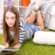 Young woman resting with book on fluffy carpet, near sofa at home — Stock Photo #41770971