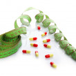 Stock Photo: Measuring tape and pills, isolated on white. Dieting concept