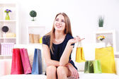 Beautiful young girl  sitting on sofa with shopping bags on home interior background — Foto de Stock