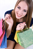 Beautiful young girl  sitting on sofa with shopping bags, close-up — Stockfoto