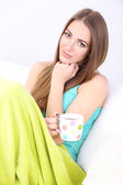Young woman resting with cup of hot drink on sofa at home — Stock Photo