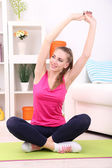 Young beautiful fitness girl exercising  at home — Stockfoto