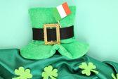 Saint patrick deixa chapéu de dia com trevo e bandeira irlandesa sobre fundo verde — Foto Stock