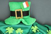Saint patrick deixa chapéu de dia com trevo e bandeira irlandesa sobre fundo cinzento — Foto Stock