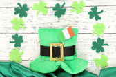 Saint Patrick day hat with clover leaves and Irish flag on wooden background — Stock Photo