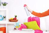 Sprayed air freshener in hand on home interior background — Stock Photo
