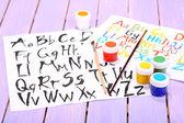 Aquarelas de alfabeto em fundo de madeira — Fotografia Stock