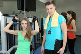 Girl and trainer engaged in simulator in gym — Stockfoto