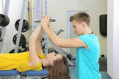 Young trainer and woman engaged with dumbbells in gym — Stockfoto