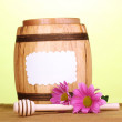 Sweet honey in barrel with drizzler on wooden table on green background — Stock Photo #41854289
